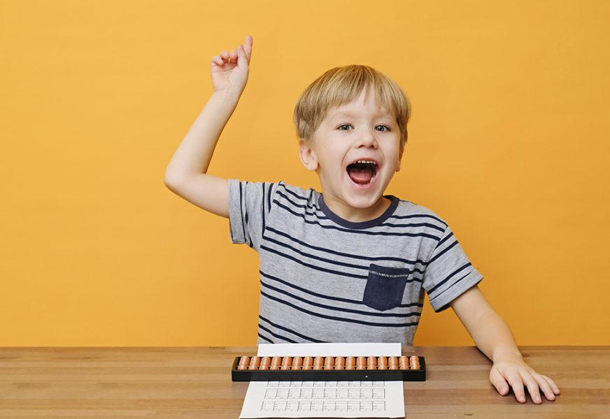 Little boy child kid doing simple math exercises with abacus scores. Mental arithmeric.